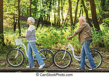 Mature husband and wife riding bikes in nature
