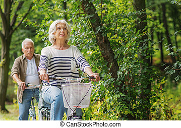 Mature husband and wife cycling in park - Cute old married...