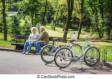 Mature man and woman resting after cycling - Old married...