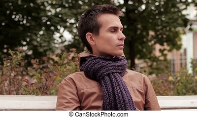 Young man with knitted scarf sitting on bench in autumn park...