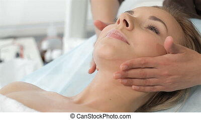 Masseur massages woman's chin - Masseur massaging woman's...