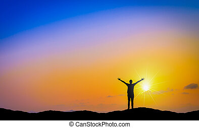 Silhouette of happy man standing on mountain at sunset.