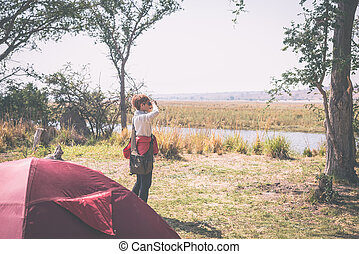 Tourist watching wildlife by binocular from camping site on...