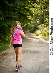 Athletic young woman carrying a javelin