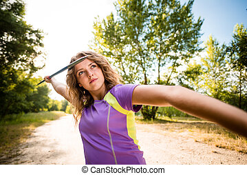 Focus - young woman throwing a javelin