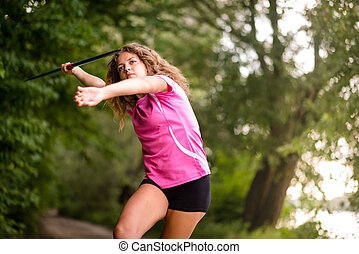 Young athlete throwing a javelin in nature