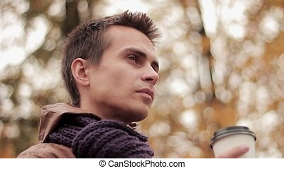 Young man in brown jacket and knitted scarf in autumn park...