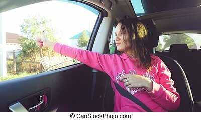 Pretty romantic woman in a car enjoying the wind, hand...