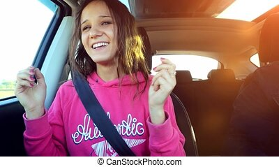 Teen beautiful girl sings and dances in the car on the...