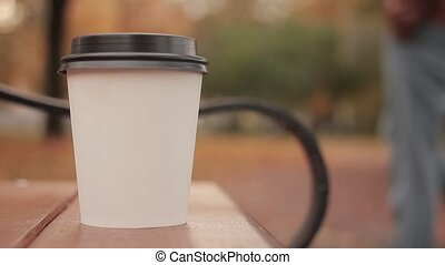 White paper cup with hot drink in autumn city park close up with defocused background skater boy walking people