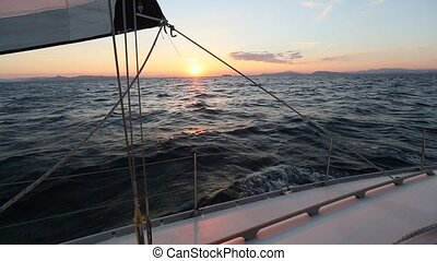 Sailing in the wind through the waves during sunset. Boat...
