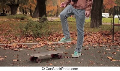 Skater while picking up skateboard continue walking slow motion