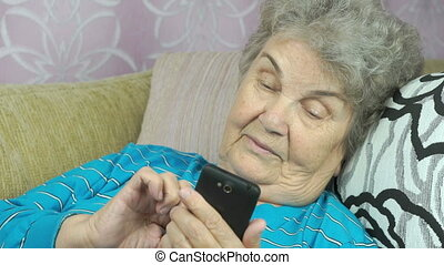 Elderly woman using a smartphone indoors
