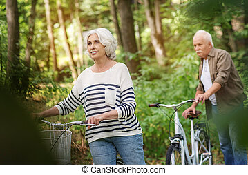 Joyful mature man and woman cycling in park - Happy old...