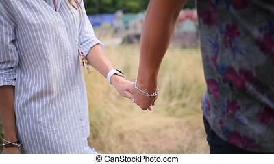 couple walking holding hands on the background