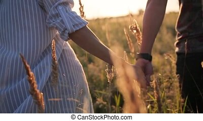 couple walking in the grass field in sun rays