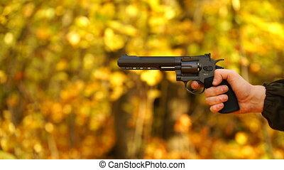 footage a man firing a revolver outdoors autumn. 4K