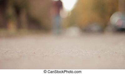 Man pushing a skateboard on asphalt road low angle extreme close shot skater moves toward the camera and turns sharply