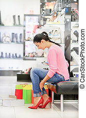 Woman fitting stilettos - Young woman fitting red elegant...