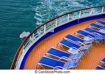 Blue sunbeds on a deck of a cruise ship