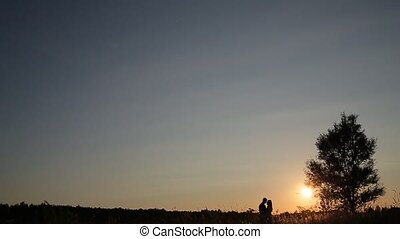couple stay in the grass field at sunset