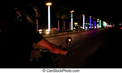 Guy Speeds on Motorcycle along Lit Street at Night - guy in...