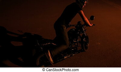 Guy in Helmet Mounts Motorcycle in Dark Street - backside...