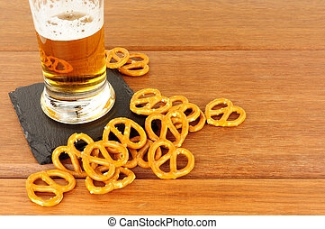 Pretzels And Lager - Pretzels and glass of lager on a wood...