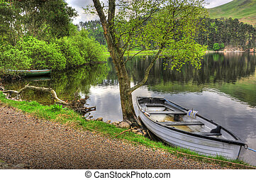rowing boat at side of lake/loch with trees hills in the...