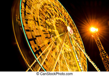 ferris wheel spinning at fairground at night with yellow...