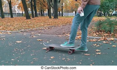 Skater picks up skateboard drops out of the hands pick up again and continue walking autumn park