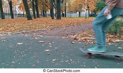 Skater pushing skateboard picking up and continue walking autumn park