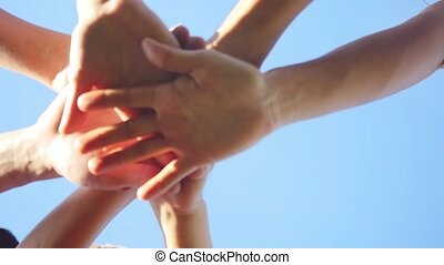 Successful team: many hands holding together on sky...