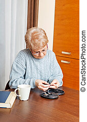 Senior woman sitting at the desk and cutting fingers nails.