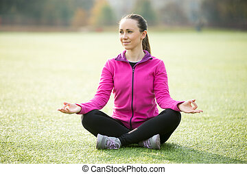Yoga outdoors: Sukhasana pose - Sporty beautiful smiling...