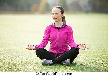 Yoga outdoors: Sukhasana pose - Sporty beautiful smiling...