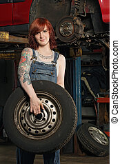 Female mechanic changing tires - Photo of a young beautiful...