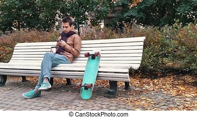 Young man with knitted scarf with skateboard sitting on bench in autumn park drinks coffee out of paper cup