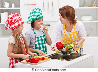 Kids and woman in the kitchen preparing the vegetables for a...