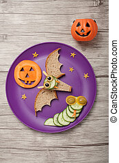 Halloween bat and snake made of bread and cucumber on plate...