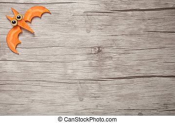 Halloween bat made of carrot on wooden background