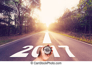 Empty asphalt road and New year 2017 concept. - Hand holding...