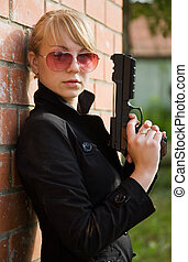 woman with gun against  the brick wall