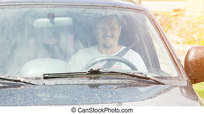 Man driving a car - Young smiling man in white T-shirt...