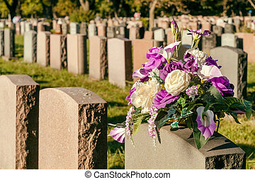Flowers in a cemetery with headstones in the background at...