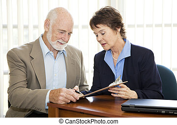 Sign on Dotted Line - Senior man signing a contract in his...