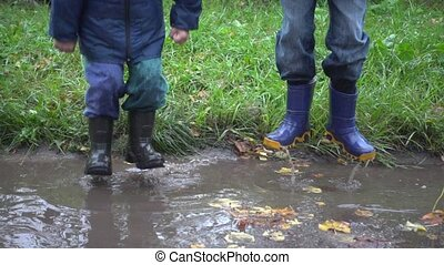 Two boys jumping in muddy puddle, slow motion 250 fps - Two...
