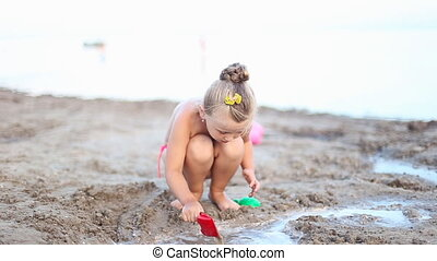 little girl playing with water on the beach