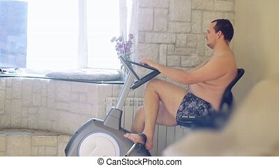 Overweight man exercising on bike simulator with...