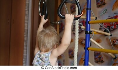 a small child is engaged in the gymnastic rings in indoor